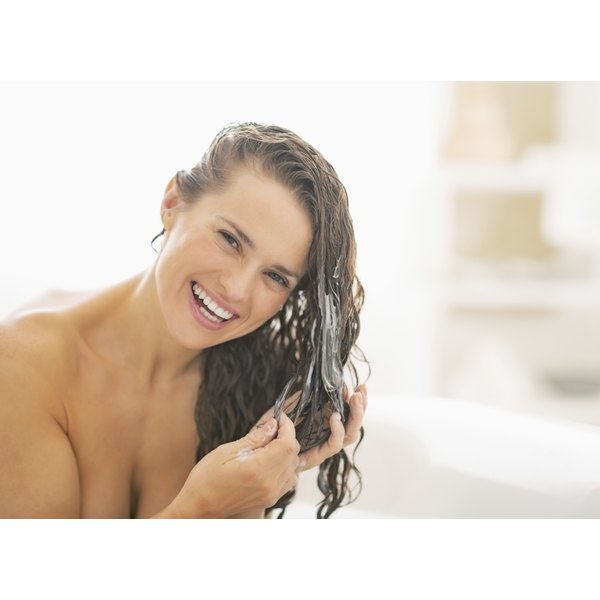 A woman is washing her hair in the shower.