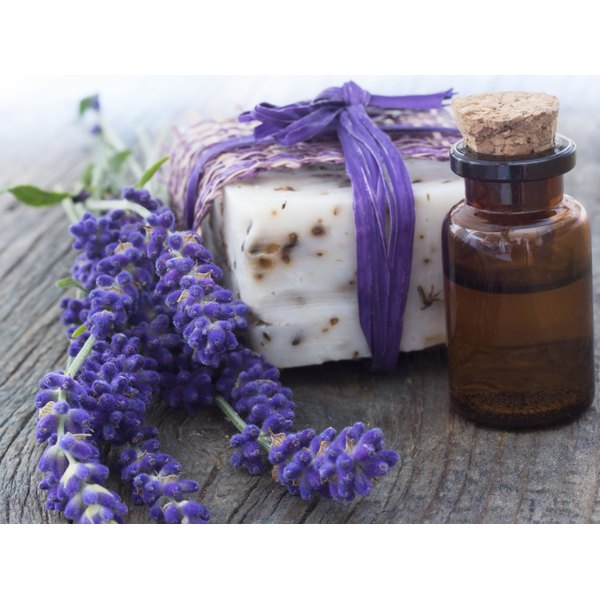 A close-up of lavendar oil and soap on a rustic table.