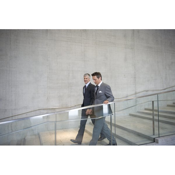 Business colleagues talking as they walk down a staircase