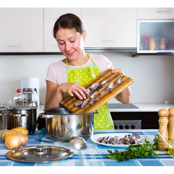 A woman cooks in the kitchen with whiting fish fillets.