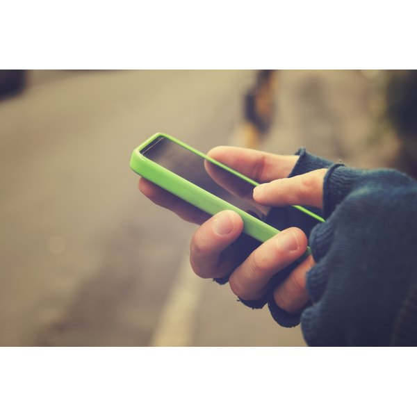 A person with fingerless gloves uses a smartphone.