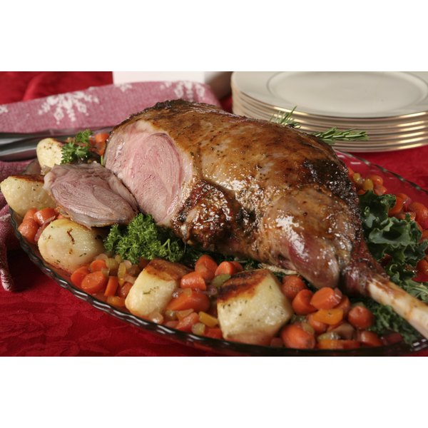 A large roasted lamb leg with vegetables.