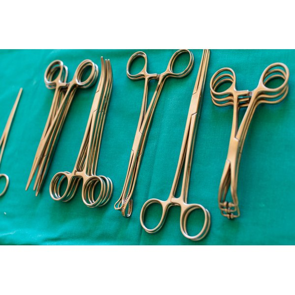 Forceps and other surgical instruments on a hospital table.