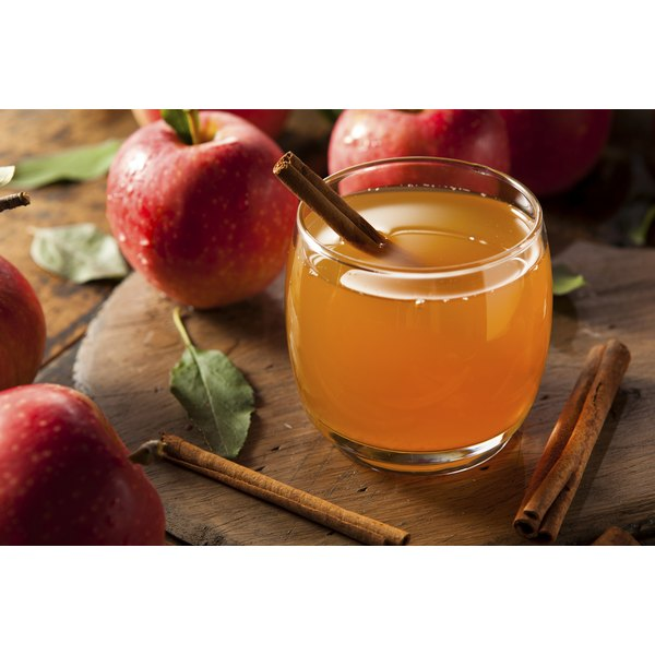 Glass of cider with a cinnamon stick next to apples
