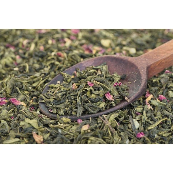 A wooden spoon sits in a pile of prickly pear tea with prickly pear flowers.