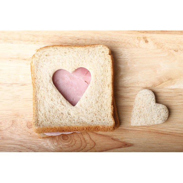 An overhead view of a ham sandwich made with wholegrain bread with a heart-shaped piece cut out of it.