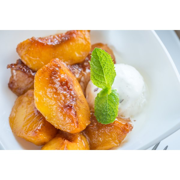 Baked peach slices in a bowl with vanilla icecream.