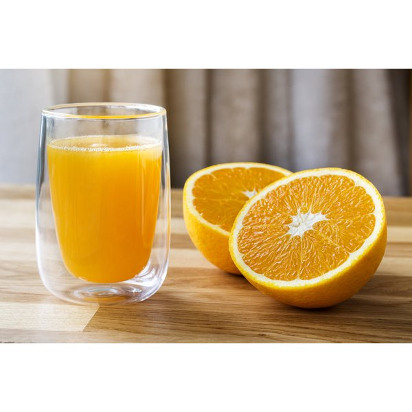 Sliced oranges and a glass of fresh juice on a table.