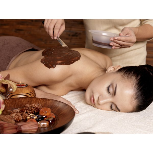 A woman is getting chocolate applied to her back.