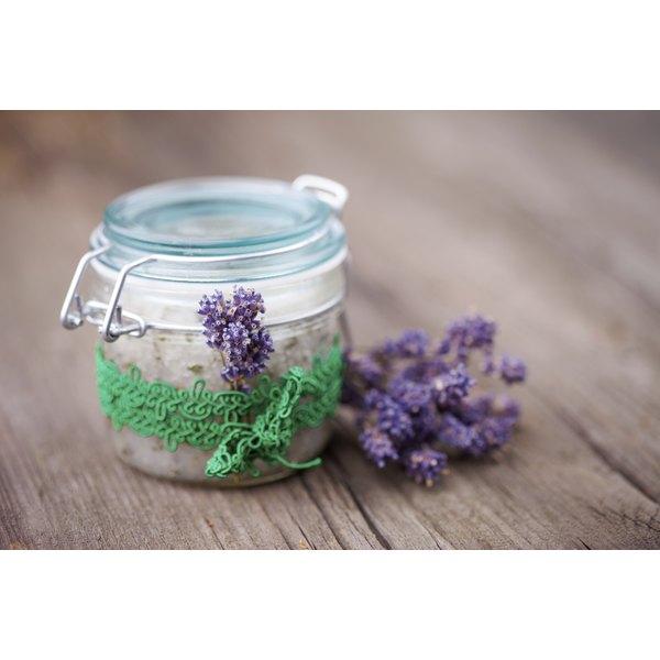 A jar of homemade body scrub on a table with fresh lavendar.