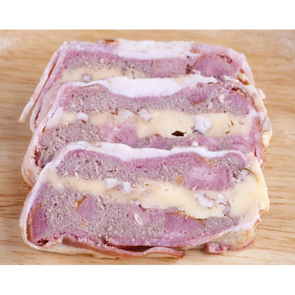 A sliced ham loaf mixed with cheese and nuts.