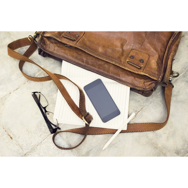 A leather bag, paper, pen and smart phone on marble.