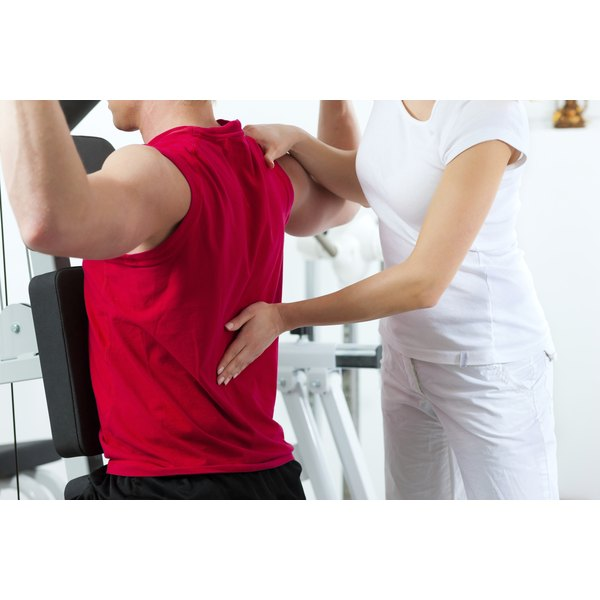 Physical therapist examines a patient's lower back as he performs exercises.