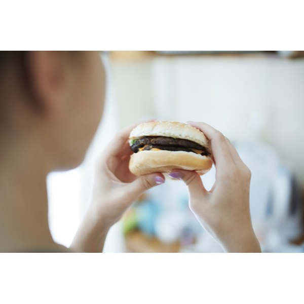 A woman about to eat a burger.
