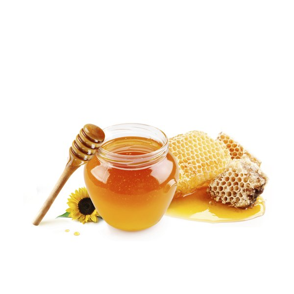 a jar of honey next to honeycomb.