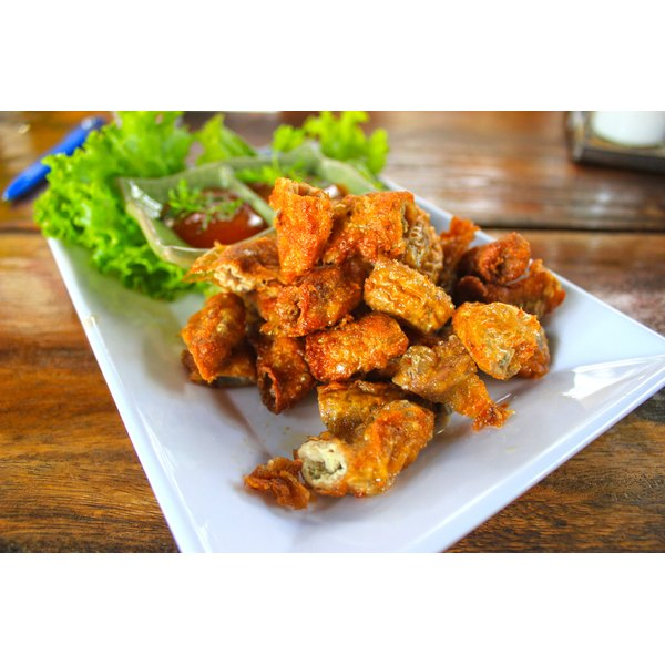 Fried pork intestine sit on a white plate on a table.
