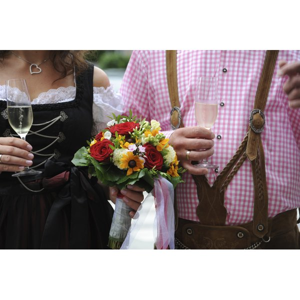 A bride and groom walking hand and hand holding champagne glasses in traditional Bavarian attire.