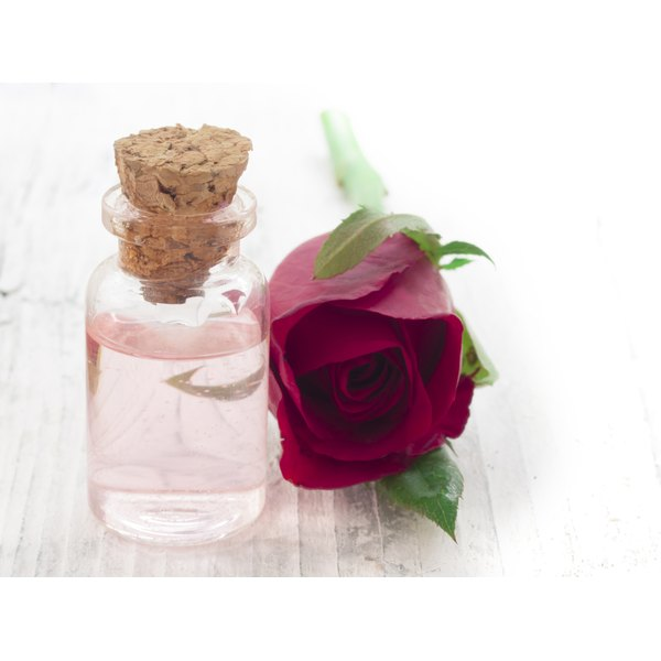 A red rose beside a bottle of rose essential oil.