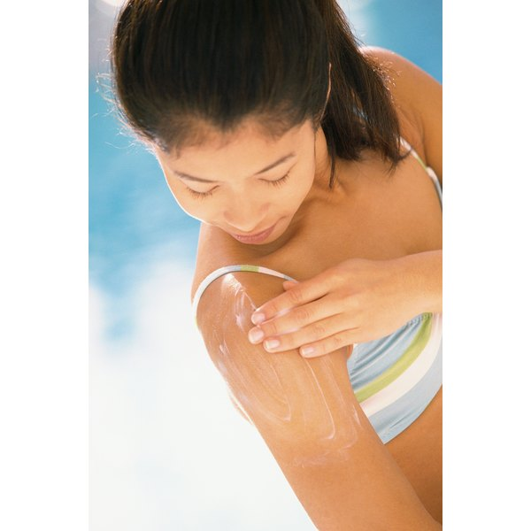 Woman rubbing suntan lotion on shoulder.