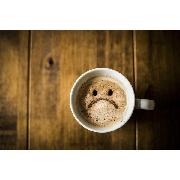A sad face in the foam of a coffee drink on an empty table.