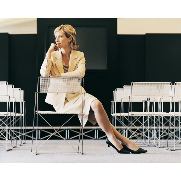 A woman in her 40s sits confidently in a room filled with seats in rows where a presentation will be given.
