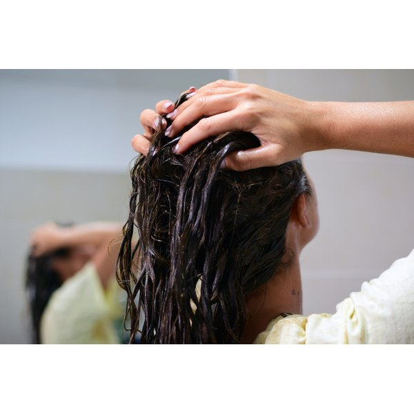 A woman massages a hot oil hair treatment into her hair.