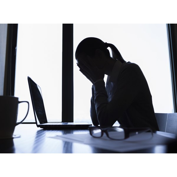 Woman at a laptop with head in her hands