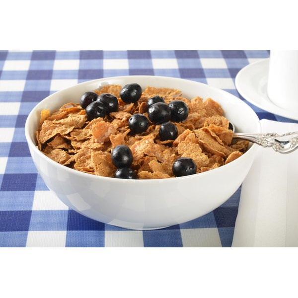 A bowl of cereal topped with blueberries.