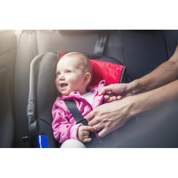 A happy toddler being buckled into a car seat.