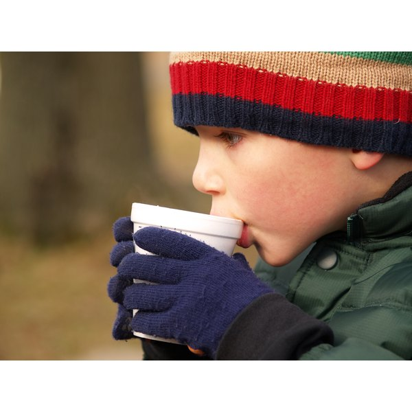 A boy drinks instant hot chocolate outside in the cold.
