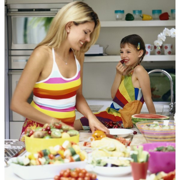 mother preparing fruits and vegetables on the counter for her daughter