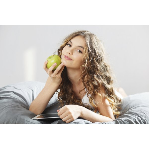 A woman is holding a green apple.