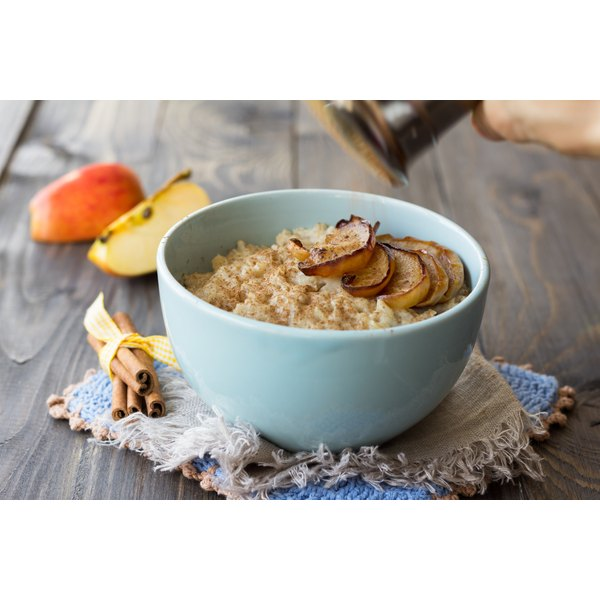 A bowl of oatmeal with apples and cinnamon.