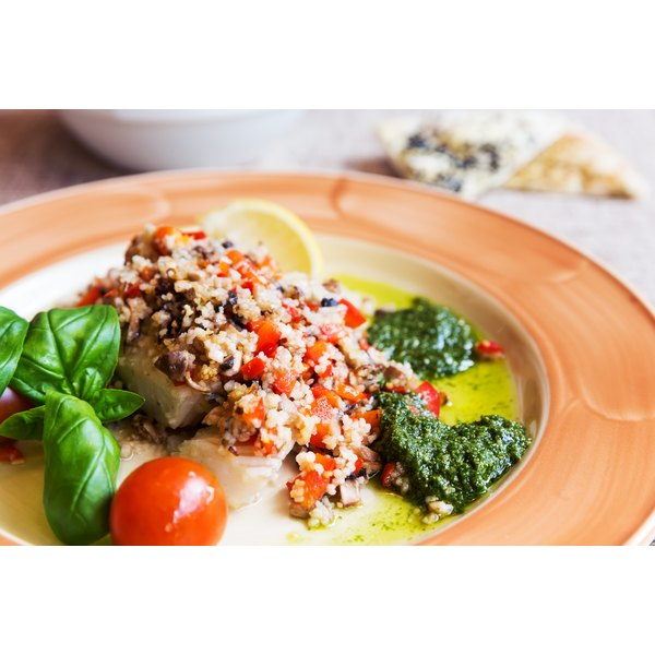 An entree of baked halibut with pesto, couscous and lemon.