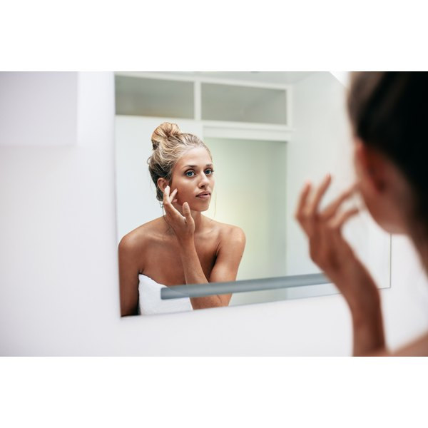 A young woman examining her face in a mirror.