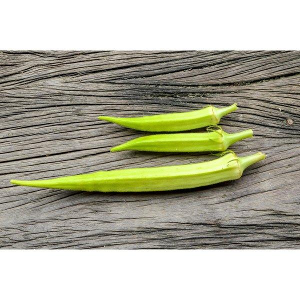 Fresh okra on a wood surface.