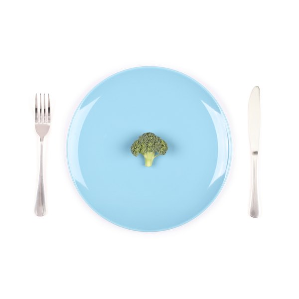 A blue plate with one piece of broccoli on it and a fork and knife beside it.