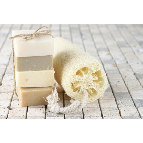 A loofah and four handmade soaps on sit on a wooden deck.