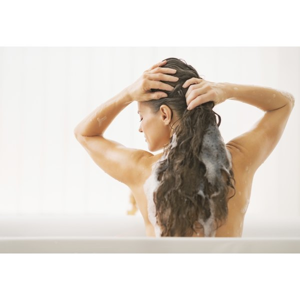 Young woman shampooing her hair.