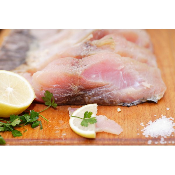 Fresh haddock fillets on a chopping board.