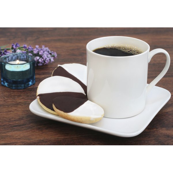 Black and white cookies on a saucer with a mug of coffee.