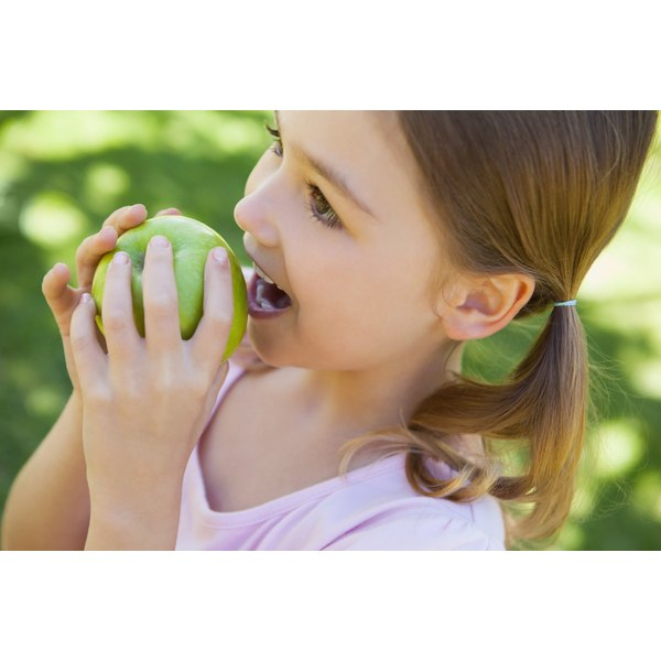 A girl biting into a green apple.