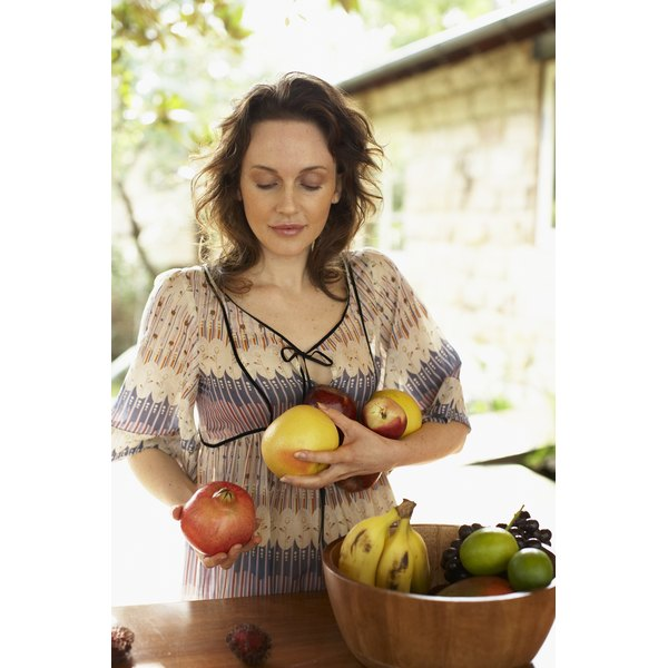 woman placing produce into bowl - looking down