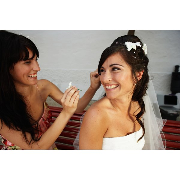 A mistress of ceremonies puts a flower into a bride's hair.
