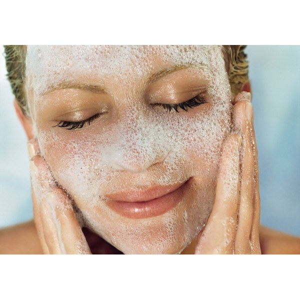 A woman washes her face with a sudsing facial cleanser.