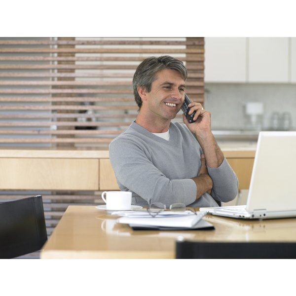 A man talking into a phone while sitting at a counter with a laptop.