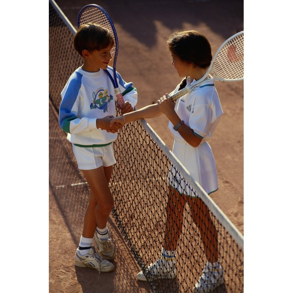 Children shaking hands over tennis net.