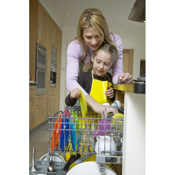 Woman showing her daughter how to load the dishwasher.