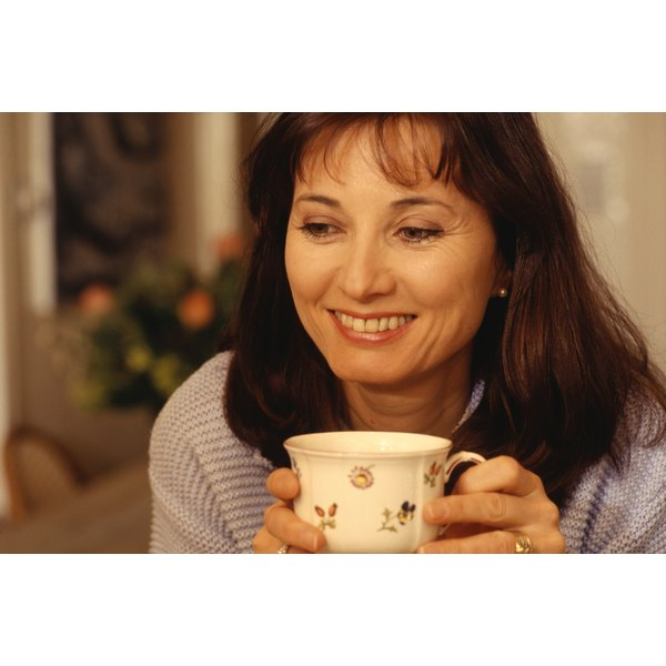 A woman drinks a cup of tea with Shaklee in it.