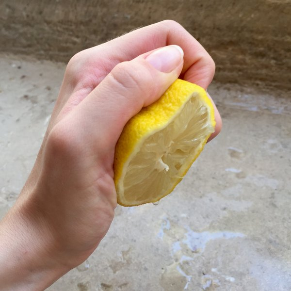 A hand squeezing a halved lemon.